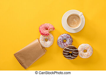 Top view of cup of coffee and several donuts scattered on yellow surface. donuts isolated on yellow background