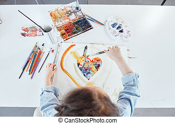 Top view of cute girl drawing using watercolor at the table