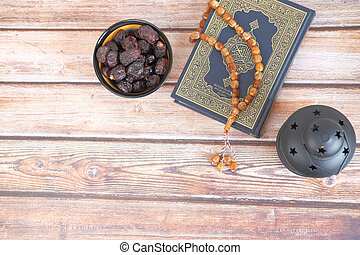 top view of date fruit , Holy book Quran and rosary on table,