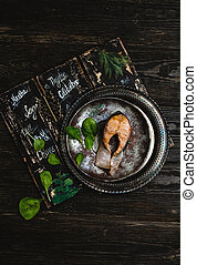 top view of delicious cooked fish with herbs on rustic wooden table