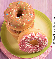 top view of delicious donuts with icing on green plate
