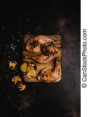 top view of delicious grilled chicken legs on wooden board