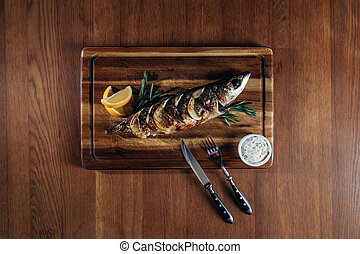 top view of delicious grilled fish with lemon on wooden board