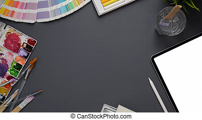 Top view of designer workspace with mock up tablet, stylus, painting tools, and copy space on grey desk