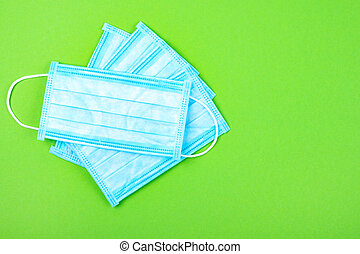 Top view of disposable medical surgical protective face mask on green background. Mask against virus, flu coronavirus.