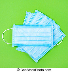 Top view of disposable medical surgical protective face mask on green background. Mask against virus, flu or coronavirus