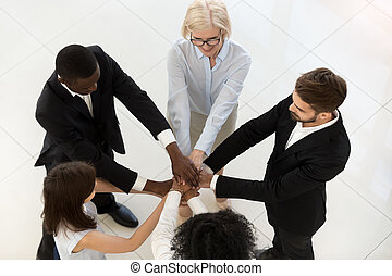 Top view of diverse employees stack hands showing unity