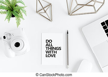 Top view of do all things with love motivational quote and instant camera at workplace