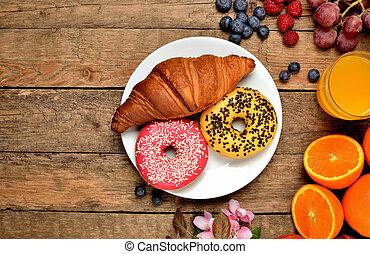 Top view of donuts, croissant, orange juice, blueberries, raspberries, apples - sweet breakfast on wooden table