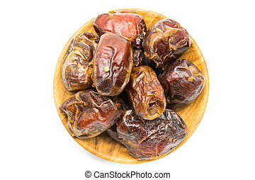 Top view of dried dates fruit in a wooden plate