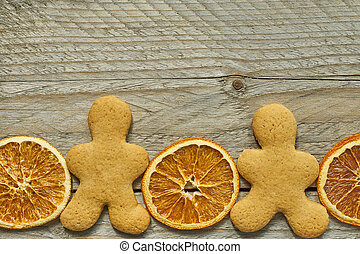 top view of dried orange slices and ginger bread man on wooden background. Festive christmas greeting card with copy space for your projects