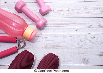 top view of dumbbell, shoe and water bottle on pink background