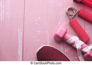 Top view of dumbbell, shoe on pink background