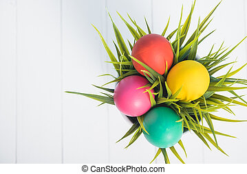 Top view of Easter eggs clean in grass on white wooden background