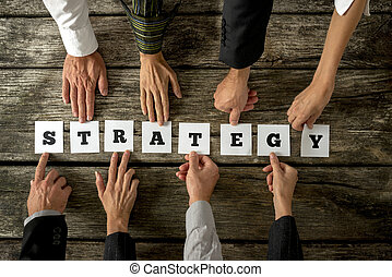 Top view of eight business people assembling the word STRATEGY