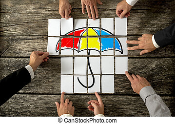 Top view of eight male hands assembling a colourful umbrella with cards