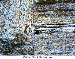 Top view of empty snowy and dark fields patched landscape on sunny winter day. Aerial drone photography concept.