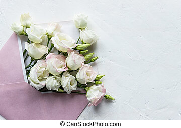 top view of eustoma and envelope with copy space on white background.card mockup with lisianthus and pink envelope. wedding invitation in minimalist style with white flowers.