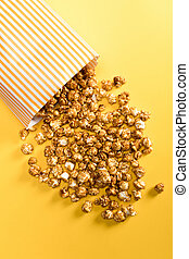 Top view of falling popcorn in box on yellow background
