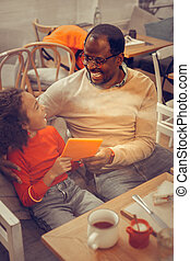 Top view of father and daughter sitting at the table in cafeteria