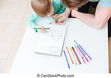 Top view of father and son drawing house together