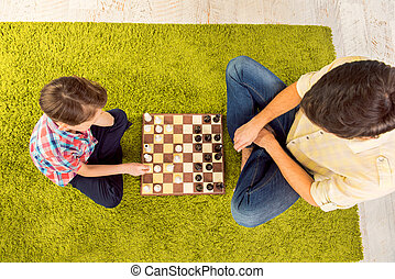 Top view of father and son sitting on carpet and playing chess