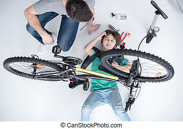 top view of father helping son with tools repairing bicycle on white