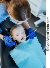 Top view of female dentist checking little patients teeth