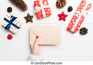 Top view of female hand holding an envelope on wooden background. New Year decorations. Christmas time concept