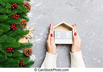 Top view of female hands holding a calendar on cement background. The twenty fifth of December. Holiday decorations. Christmas concept