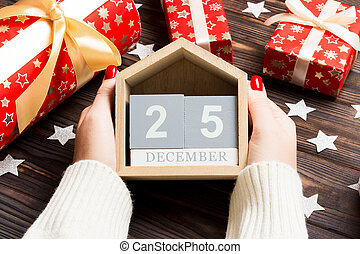 Top view of female hands holding a calendar on wooden background. The twenty fifth of December. Holiday decorations. Christmas concept