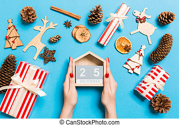 Top view of female hands holding calendar on blue background. The twenty fifth of December. Holiday decorations. Christmas time concept