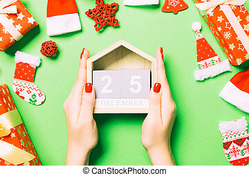 Top view of female hands holding calendar on green background. The twenty fifth of December. Holiday decorations. Christmas time concept