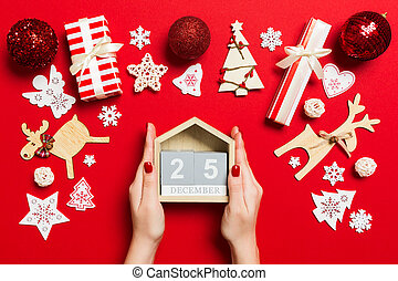 Top view of female hands holding calendar on red background. The twenty fifth of December. Holiday decorations. Christmas time concept