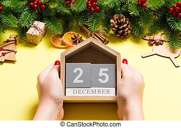 Top view of female hands holding calendar on yellow background. The twenty fifth of December. Holiday decorations. Christmas time concept