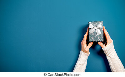 top view of female hands holding Christmas gift