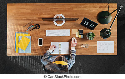 Top view of female student working on computer at desk at home.