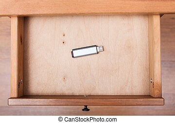 flash drive in open drawer of nightstand