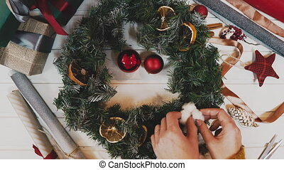 top view of florist hands making Christmas wreath on wooden...