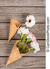 top view of flowers in sugar cones laying on wooden table, wooden background