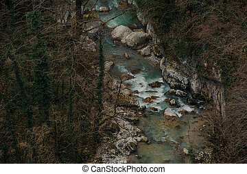 Top view of forest river flowing among rocks in Martvili canyon