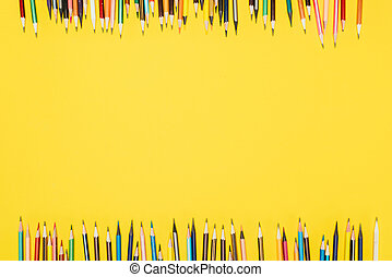 Top view of frame of colorful pencils isolated on yellow background