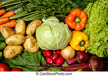 Top view of fresh assorted vegetables on dark black background