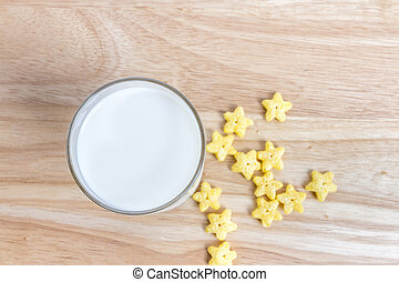 Top view of fresh milk in glass with star cereals on the wooden table