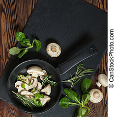 Top view of fresh mushrooms with mash salad and rosemary on a dark frying pan setting on a black stoned board on a wooden table. Copy space