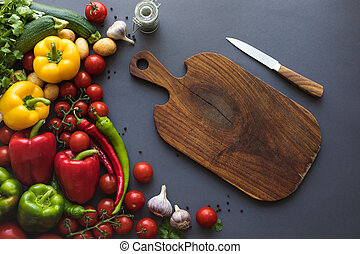 top view of fresh ripe vegetables with cutting board and knife on grey