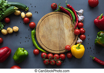 top view of fresh ripe vegetables with wooden cutting board on grey
