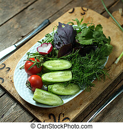 top view of fresh salad with cucumbers tomatoes and herbs on a plate on wooden background