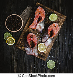 top view of fresh sliced red fish with spices and citrus fruits on rustic wooden table