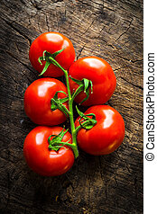Top view of fresh tomatoes on wooden background